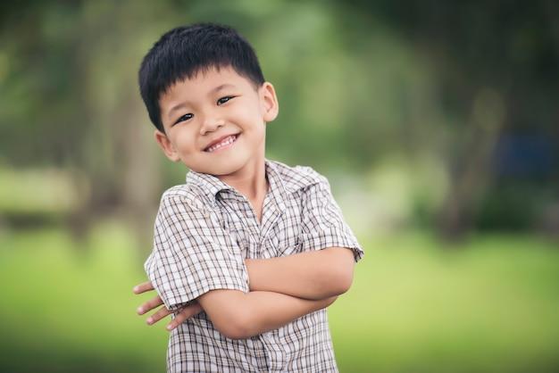 Portret śliczna chłopiec pozycja z rękami składał kamerę i patrzeje