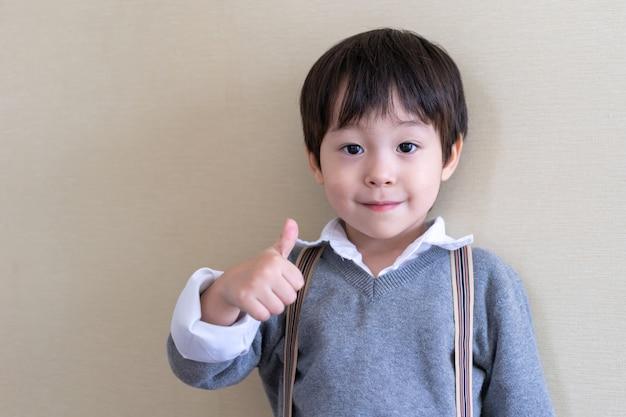 Portret śliczna chłopiec stoi i uderza w górę