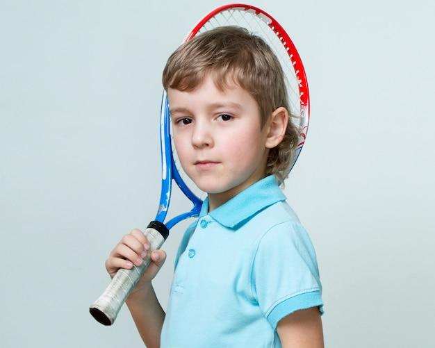 Portret śliczna chłopiec trzyma tenisową rakietę