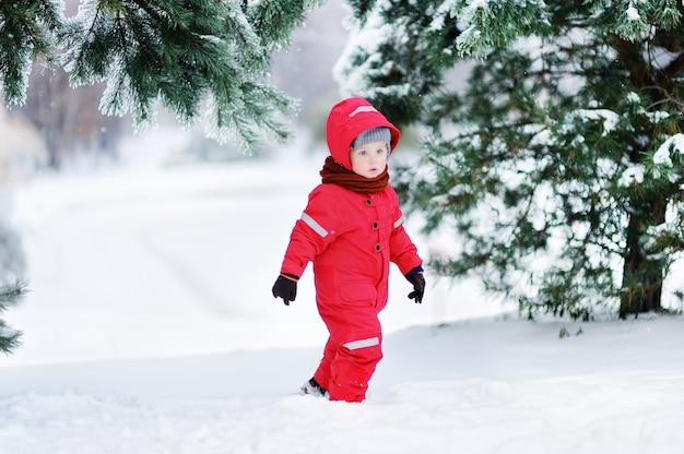Portret śliczna chłopiec w czerwonych zim ubraniach ma zabawę z śniegiem. aktywny wypoczynek na świeżym powietrzu z dziećmi zimą. dziecko z ciepłą czapką, rękawiczkami i szalikiem