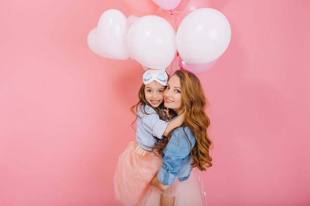 Portret śliczna długowłosa mała urodzinowa dziewczynka z białymi balonami obejmująca jej młodą kędzierzawą mamę po wydarzeniu. urocza matka pozuje z ładną córką na imprezie na białym tle na różowym tle