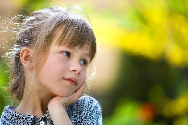 Portret śliczna dosyć rozważna dziecko dziewczyna outdoors na zamazany pogodny kolorowy jaskrawym.