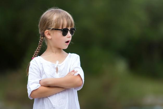 Portret śliczna dosyć śmieszna młoda dziewczyna z blond warkoczami w biel sukni i ciemnych okularach przeciwsłonecznych.