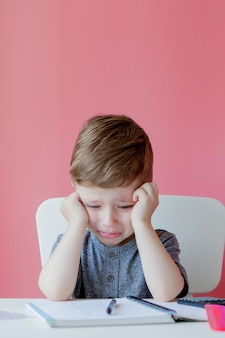 Portret śliczna dzieciak chłopiec robi pracie domowej w domu. mały skoncentrowany dziecko pisze z kolorowym ołówkiem, indoors. szkoła podstawowa i edukacja.