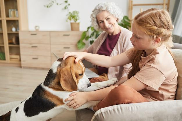 Portret śliczna dziewczyna bawi się z psem, ciesząc się czasem z rodziną w przytulnym wnętrzu domu