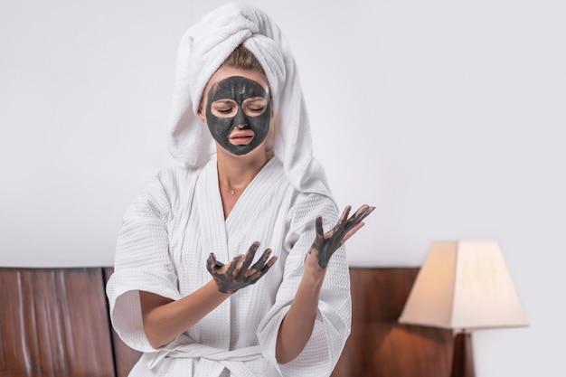 Portret śliczna dziewczyna pozuje w glinianej masce z glinianymi rękami w białym szlafroku i ręcznikiem na jej głowie pozuje patrzeć w dół. pojęcie relaksu.