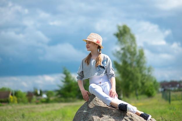 Portret śliczna dziewczyna siedzi na dużym kamieniu na błękitnym niebie
