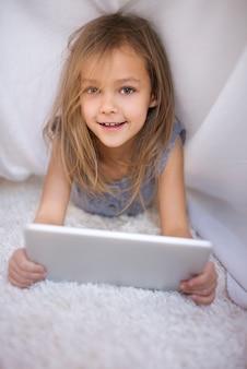 Portret śliczna dziewczyna trzyma cyfrowy tablet