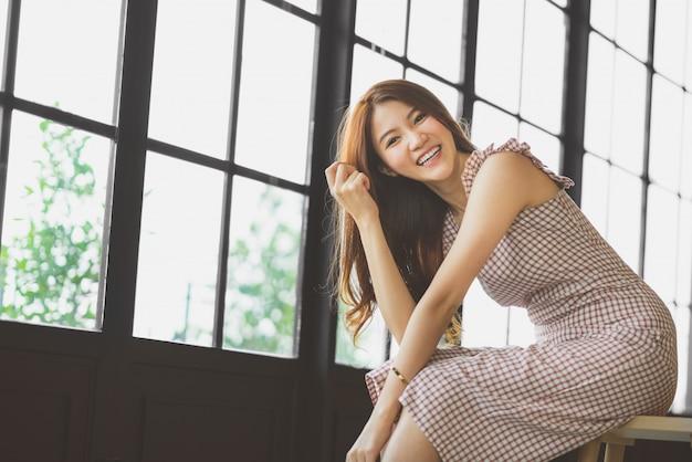 Portret śliczna i piękna azjatycka dziewczyna ono uśmiecha się w sklep z kawą lub nowożytnym biurze z kopii przestrzenią