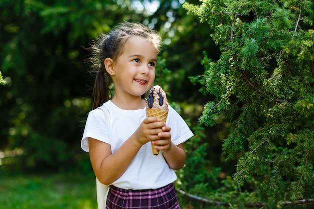 Portret śliczna i szczęśliwa mała dziewczynka liże lody outside. pyszne lody.