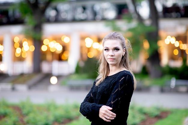 Portret śliczna i wspaniała młoda kobieta na niewyraźne tło ulicy z światłem bokeh