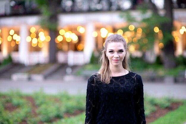 Portret śliczna i wspaniała młoda kobieta na rozmytym tle strret z światłem bokeh