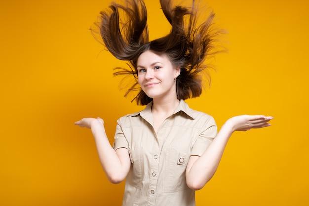 Portret śliczna kaukaska uśmiechnięta dziewczyna, zdumiony, pokazując podekscytowanie, włosy wiejący wiatr. na białym tle na żółtym tle