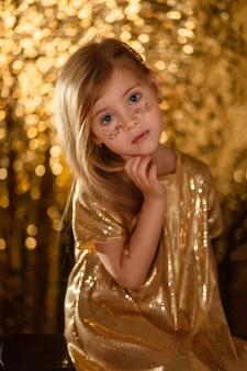 Portret śliczna mała blondynka z długimi włosami w złotej sukni na złotym tle bokeh.