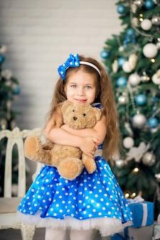 Portret śliczna mała dziewczynka blisko choinki. pozowanie z misiem, któremu na prezent świąteczny został jej podarowany prezent.