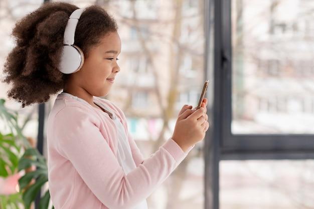 Portret śliczna mała dziewczynka słucha muzyka