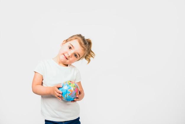 Portret śliczna mała dziewczynka trzyma kuli ziemskiej przeciw białemu tłu