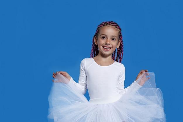 Portret śliczna mała dziewczynka w białej sukni tańczy jak baletnica, na niebieskiej przestrzeni. miejsce na tekst.