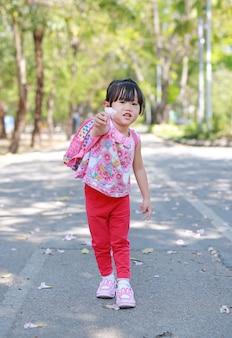 Portret śliczna mała dziewczynka w jawnym parku z mienie kwiatem dla ciebie.