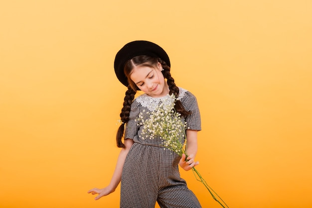 Portret śliczna mała dziewczynka z bukietem kwiatów w studio na żółtym tle. congratulation, spring or happy holiday concept. skopiuj miejsce na tekst