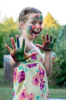 Portret śliczna mała dziewczynka z malującą twarzą i rękami