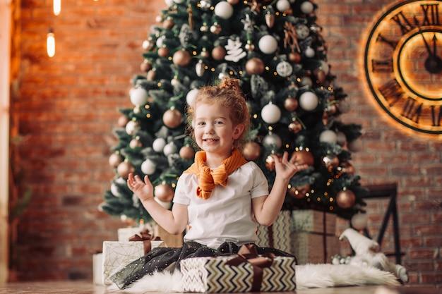 Portret śliczna mała dziewczynka z prezentami bożonarodzeniowymi. koncepcja bożego narodzenia
