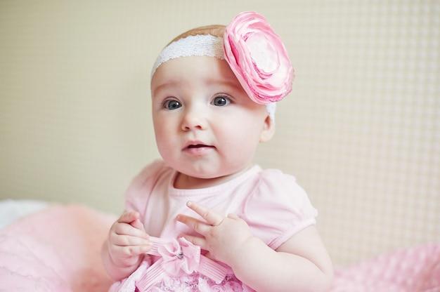 Portret śliczna mała dziewczynka z różowym kwiatem łuk na głowie.