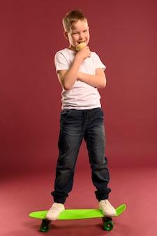 Portret śliczna młoda chłopiec pozuje z deskorolka