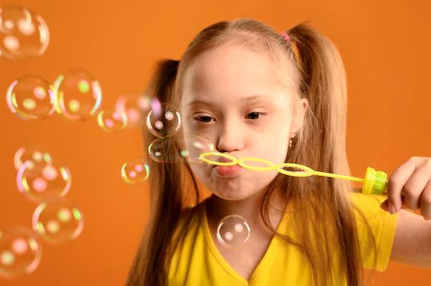Portret śliczna młoda dziewczyna dmucha bąble