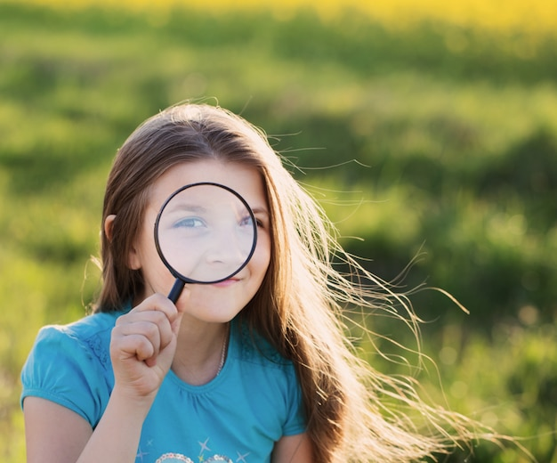 Portret śliczna młoda dziewczyna patrzeje przez powiększać - szkło