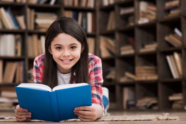 Portret śliczna młoda dziewczyna trzyma książkę