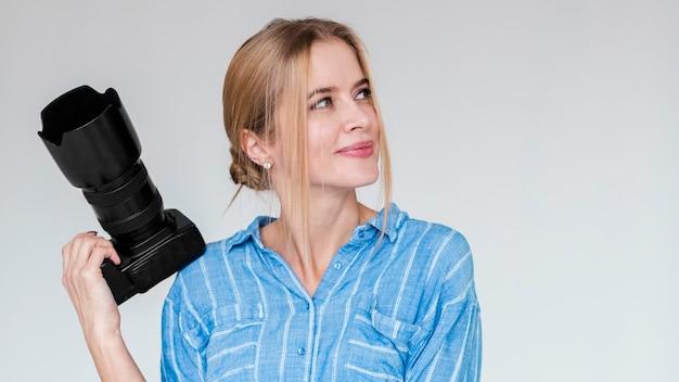 Portret śliczna młoda kobieta trzyma kamerę