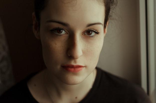 Portret śliczna młoda kobieta z dużymi brown oczami i piegami. biała skóra. piękny.