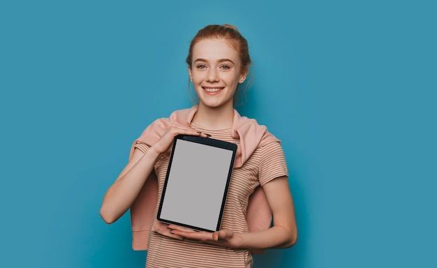 Portret śliczna młoda kobieta z rudymi włosami i piegami trzyma tablet pokazując biały ekran patrząc na aparat uśmiechnięty na białym tle na niebieskim tle.