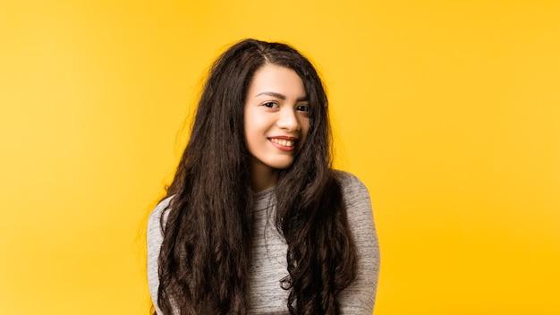 Portret śliczna, nieśmiała brunetka dziewczyna z długimi włosami. słodka emocjonalna dama o zachwyconym, przyjaznym wyrazie twarzy.
