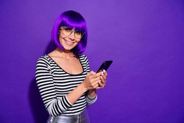 Portret śliczna osoba z fioletową grzywką trzymając nowoczesną technologię patrząc na białym tle na fioletowym tle