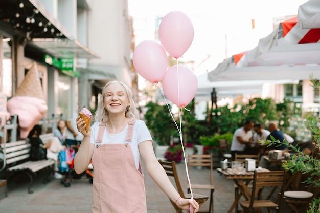 Portret śliczna pani idąca ulicą z lodami i balonami