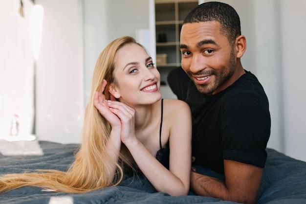 Portret śliczna para zakochanych, chłodzenie na łóżku rano w nowoczesnym mieszkaniu. uśmiechnięta młoda kobieta z długimi blond włosami bawi się z przystojnym facetem. prawdziwe emocje, miłość, razem