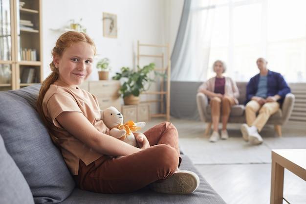Portret śliczna rudowłosa dziewczyna siedzi na kanapie w przytulnym salonie z dziadkami