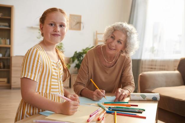 Portret śliczna rudowłosa dziewczyna uśmiecha się radośnie podczas rysowania razem z babcią, ciesząc się czasem w domu
