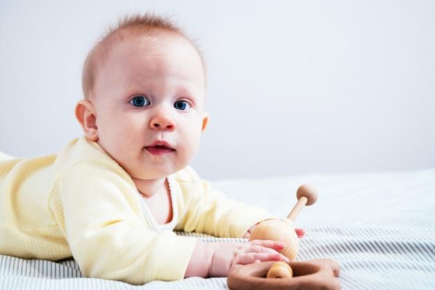 Portret śliczna siedmiomiesięczna dziewczyna o niebieskich oczach. dziecko bawi się drewnianymi zabawkami w jasnym pokoju. ekologiczne zabawki dla dzieci wykonane z naturalnych materiałów.
