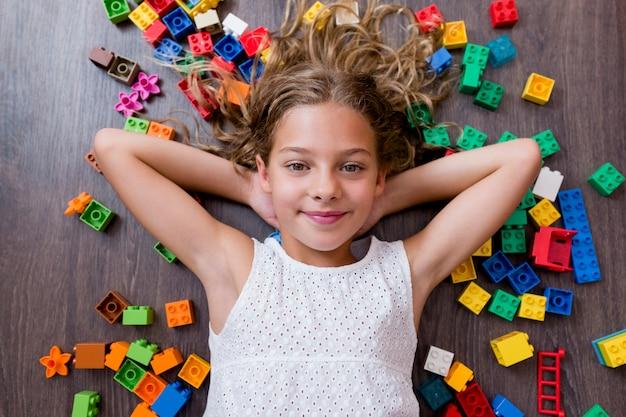 Portret śliczna śmieszna preteen dziewczyna bawić się z budowy zabawki blokami. leżąc na drewnianej podłodze w otoczeniu kolorowych klocków dzieci bawiące się.