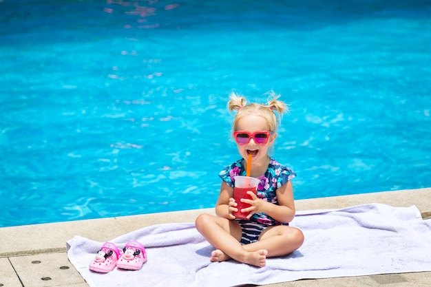Portret śliczna szczęśliwa mała dziewczynka ma zabawę w pływackim basenie i pije świeżego arbuza sok
