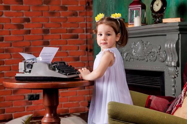 Portret śliczna trzyletnia dziewczyna w salonie pisania na starej maszynie do pisania. studio strzałów na małą sekretarkę dziecka w tle. pojęcie ciężkiej pracy i wykonywania obowiązków służbowych. skopiuj miejsce