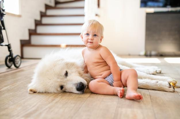 Portret śliczna urocza mała blondynka chłopiec siedzi z psem w domu. uśmiechnięte dziecko trzyma zwierzę domowe zwierzę domowe. koncepcja szczęśliwego dzieciństwa