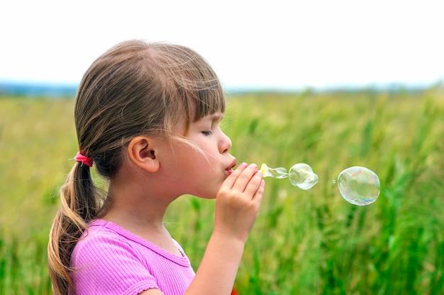 Portret śliczna urocza mała dziewczynka dmucha mydlanych bąble
