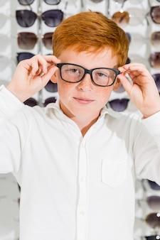 Portret śliczna uśmiechnięta chłopiec jest ubranym widowiskowego patrzeje kamerę