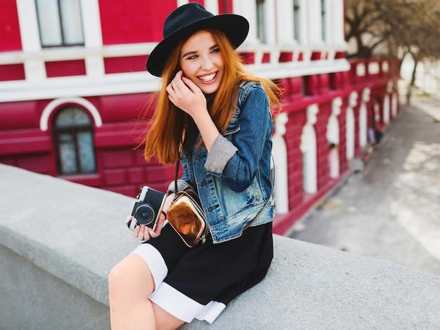 Portret śliczna wesoła młoda kobieta z niesamowitymi rudymi włosami, pozowanie na ulicy, trzymając retro filmową kamerę