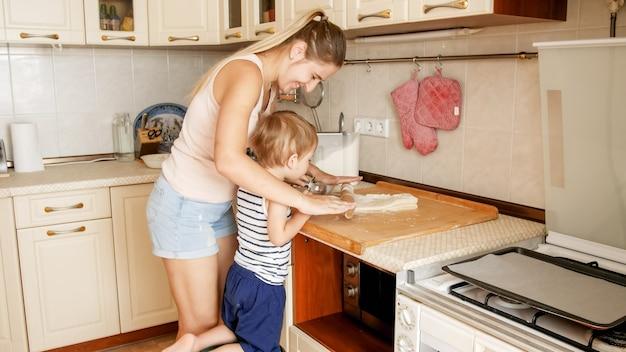 Portret ślicznego 3-letniego chłopca gotującego ciasteczka z matką
