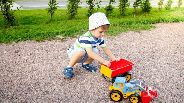 Portret ślicznego 3-letniego chłopca siedzącego na placu zabaw w parku i bawiącego się kolorową ciężarówką z tworzywa sztucznego